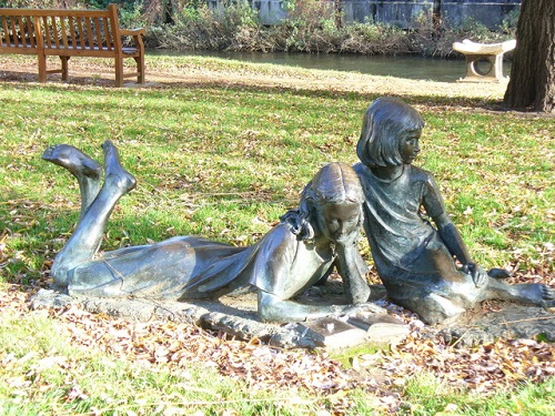 Bronze sculptures by the riverside in Guildford, showing children reading Alice in Wonderland (Image source: Wikimedia Commons CC BY-SA 2.0 | Credit to: Colin Smith)